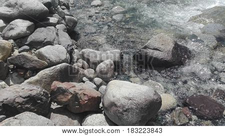 A river of fresh water among the rocks. Fresh aqua fast flow in the stones. A forest river with clean cold water. Fresh spring in the mountains. Concept of drinking water. Rapid flow of water in the wild