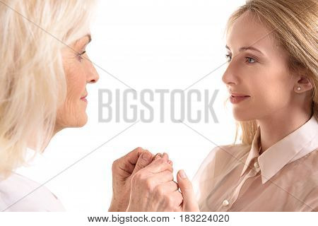 Invisible support. Old mother and her daughter are holding hands. They looking at each other with kindness