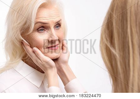 Kind glance. Woman is putting hands on face of old lady. She looking with smile. Isolated