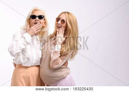 Happy smiling mother and daughter in sunny glasses are standing together, looking at camera. Copy space on right side. Isolated