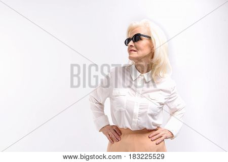 Modern mature lady wearing sunglasses is standing and looking aside with smile. Portrait. Isolated. Copy space on left side