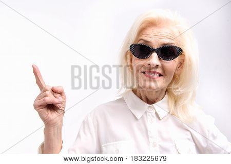 I have got idea. Mature lady in sunglasses is looking at camera with bright smile and pointing up. Portrait. Isolated. Copy space on left side