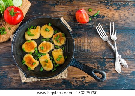 Crisp chicken nuggets with green onion in black cast iron skillet vintage forks and fresh tomatoes and cucumbers on the cutting board. Wooden table top view.