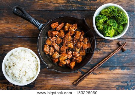 Chicken teriyaki pan-fried in a cast iron skillet with garnish of rice and broccoli in white bowls. Chopsticks wooden rustic table top view.