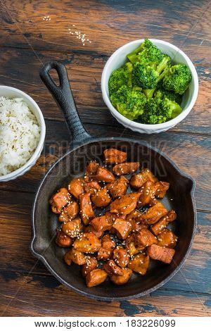 Chicken teriyaki pan-fried in a cast iron skillet with garnish of rice and broccoli in white bowls. Wooden dark rustic table top view vertical photo.