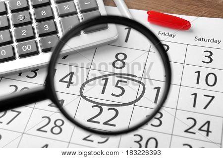 Magnifying glass over calendar, closeup