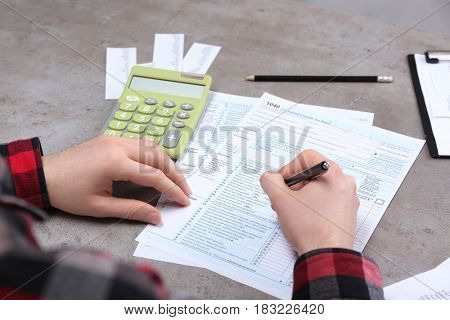 Man working with documents and calculator. Tax concept