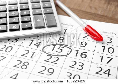 Calculator with pen on calendar. Tax concept
