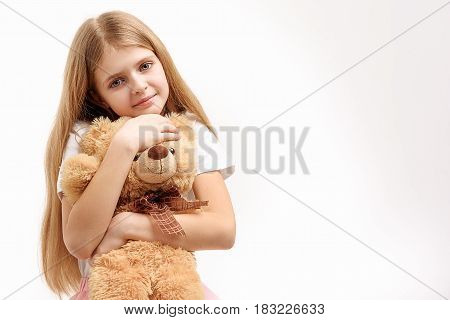 Small girl is hugging soft toylike bear and looking at camera with smile. Portrait. Isolated. Copy space on right side