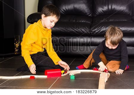 Children playing with wooden toy train. Brothers build wooden railroad at home.