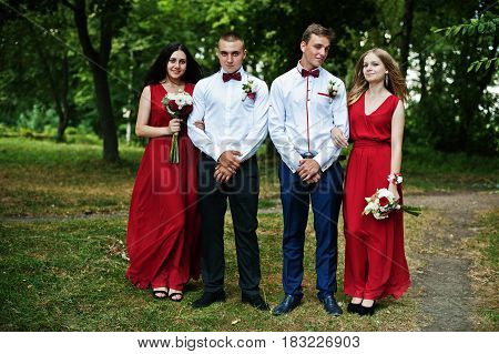 Bridesmaids At Red Dresses With Groomsman Or Best Man At Wedding.