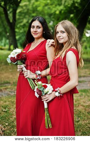 Two Girls Bridesmaids At Red Dresses With Wedding Bouquets.