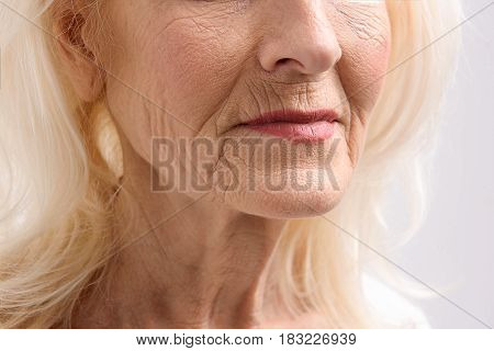 Close up of Furrows on face of old lady. Focus at her chin. Isolated