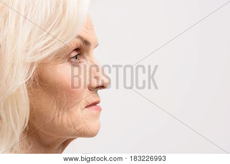 Age changes. Old lady is looking ahead with seriousness. Profile. Copy space on right side