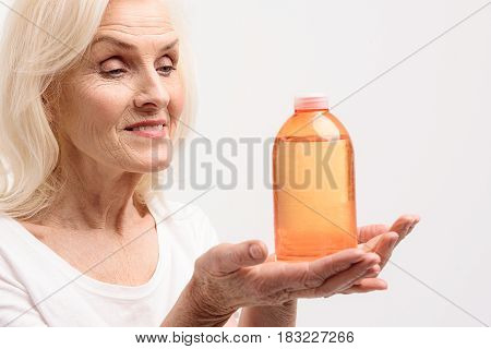 Cheerful mature woman is holding shower gel in orange bottle and looking at it with smile. Isolated