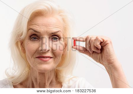 Smiling old lady is holding read pill and looking at camera with relief. Portrait. Isolated