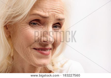 Smiling mature lady with wrinkled face is looking at camera with interest. Portrait. Isolated. Copy space on right side
