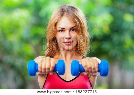 Active sporty woman doing morning exercises with dumbbells at home. Workout plan to get summer beach body. Healthy lifestyle fitness exercises to keep fit loss weight and shaping perfect slim body.