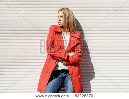 Cool blond girl waiting for someone on street. She is leaning on wall and looking aside with surprise. Lady is wearing red spring coat