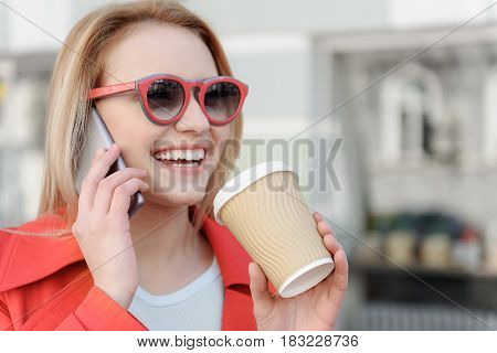 Portrait of happy blond girl drinking coffee with relaxation outdoors. She is communicating on phone and smiling. Lady is wearing red eyeglasses and coat. Copy space