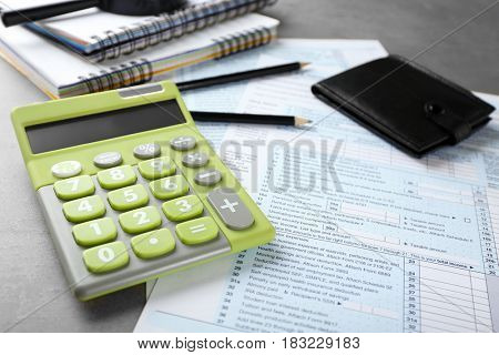 Green calculator with documents on table. Tax concept