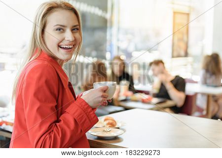 Portrait of excited blond girl drinking coffee in cafeteria. She is sitting at table with pastry on it. Lady is looking at camera and laughing