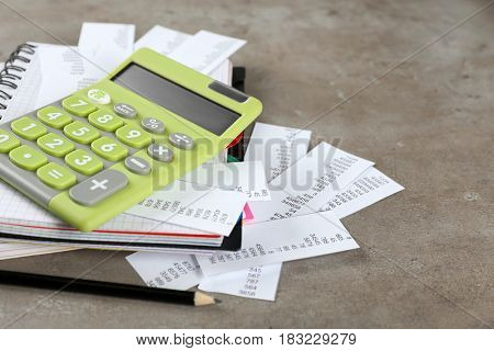 Green calculator with bills and notebook on gray background. Tax concept