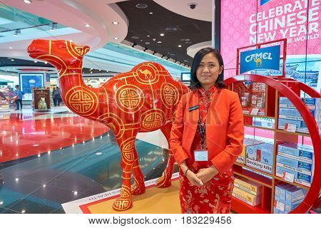 DUBAI, UAE - CIRCA JANUARY, 2017: indoor portrait of promouter in red asian style clothing at Dubai International Airport. The airport is home to the long-haul carrier Emirates.