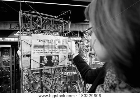 PARIS FRANCE - APRIL 24: Woman buy looks at press kiosk at UK newspaper with pictures of French Presidential election candidates Emmanuel Macron Marine Le Pen a day after first round of French Presidential election on April 23 2017