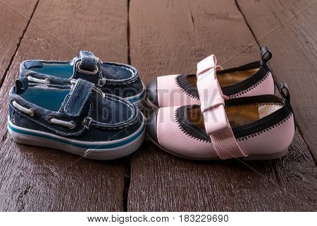 Baby Boy And Girl Shoes On Wooden Background. Child Footwear.