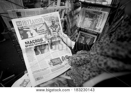 PARIS FRANCE - APRIL 24: Woman buy looks at press kiosk at Dutch het laatste nieuws newspaper pictures of French Presidential election candidates Emmanuel Macron Marine Le Pen a day after first round of French Presidential election on April 23 2017