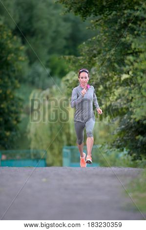 Runner female athlete running on park trail. Woman fitness jogging workout wellness concept.
