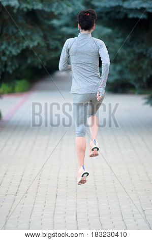 Runner athlete running on city Alley. Woman fitness jogging workout wellness concept.