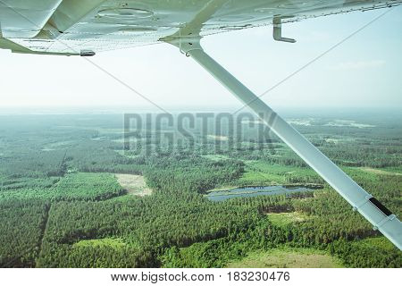 View to the rural lanscape from the board of a light plane while flying over the forest