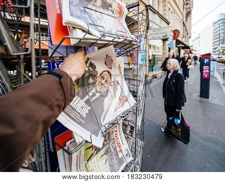 PARIS FRANCE - APRIL 24: Man buy looks at press kiosk at French newspaper Liberation with pictures of French Presidential election candidates Emmanuel Macron a day after first round of French Presidential election on April 23 2017