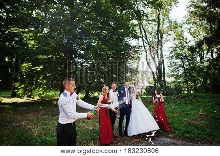 Wedding Couple With Bridesmaids And Best Mans Drinking Champagne Outdoor