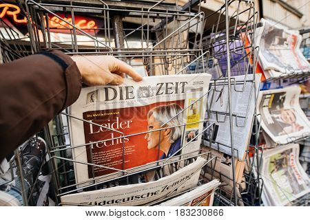 PARIS FRANCE - APRIL 24: Man buy looks at press kiosk at German Die Zeit newspaper with pictures of French Presidential election candidates Marine Le Pen a day after first round of French Presidential election on April 23 2017