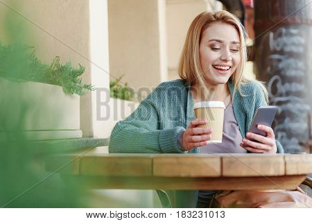 Portrait of cheerful blond girl enjoying online communication. She is sitting outdoor the cafeteria and drinking coffee. Lady is looking at screen and smiling