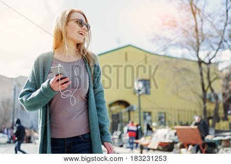 Low angle of happy young woman walking in town with enjoyment. She is listening to music from smartphone playlist and laughing