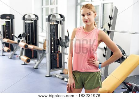 First day in fitness center. Portrait of serene woman standing in wide room with different types of equipment in it. Sport concept