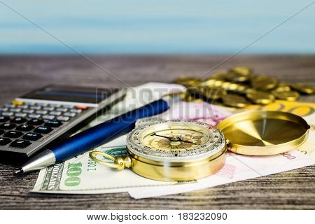 Composition of a tourist compassbanknotescoinscalculator and pen on the gray wooden table at background of the sea