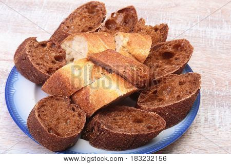 Sliced bread Ciabatta with plate on cutting board on wooden background.