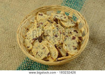 Oat and cranberry crispbread snack in wooden wicker basket