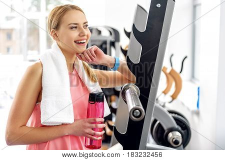 Portrait of girl demonstrating happiness while reclining against fitness tool in health club. She is carrying towel and bottle