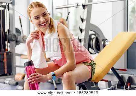 Low angle woman expressing cheeriness while sitting on weight bench in workout room. She drinking water