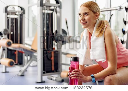 Female showing happiness while locating in fitness center. She holding shaker in hand