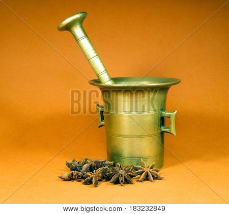 Old bronze mortarwith star-anise spice on yellow background
