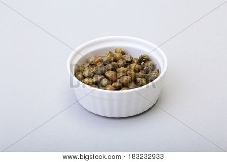 bowl with fresh capers isolated on white background
