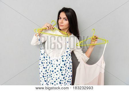 Brunette woman choosing between two beautiful dresses isolated
