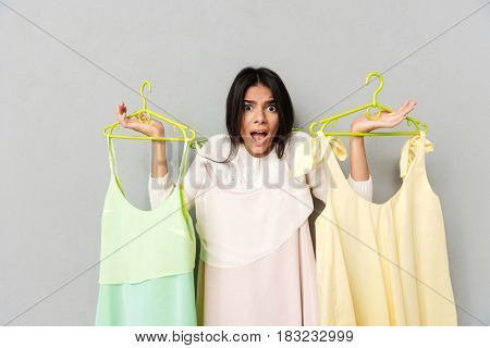Shocked young woman holding dresses on hangers isolated